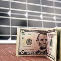 American dollars in front of solar panels, solar savings