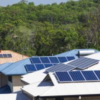 multiple solar panels on a few houses in a neighborhood