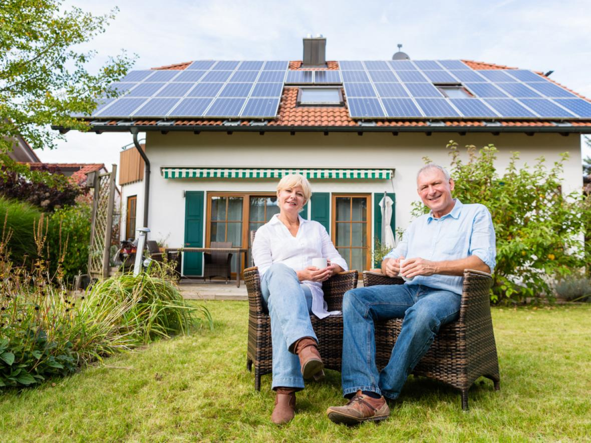 couple seated in front of home with solar panels on roof