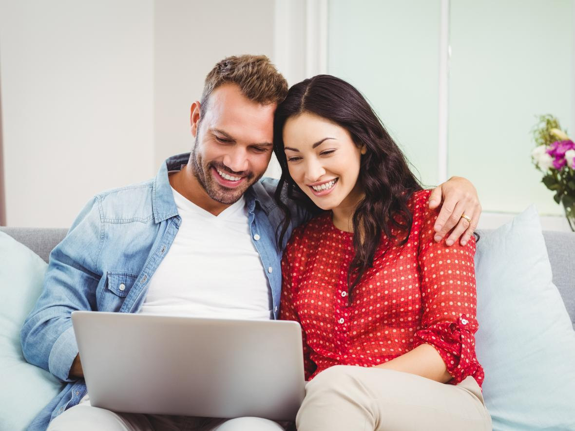 man and woman on looking on laptop together