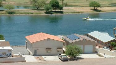 row of homes with solar power next to water