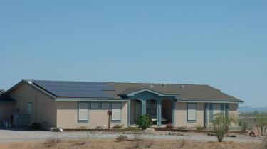 ranch style home with solar system on roof
